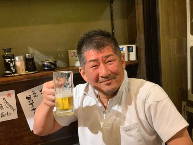 ビールを持って笑う男性の画像
